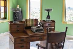 Skrivbordet i de olden dagarna Den gamla skrivmaskinen och böckerna är in royaltyfria bilder