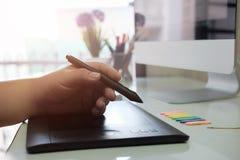 skrivbordhanden för den grafiska designen som använder muspannan, skissar apparaten royaltyfri bild