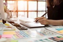 skrivbordhanden för den grafiska designen som använder muspannan, skissar apparaten på creati fotografering för bildbyråer