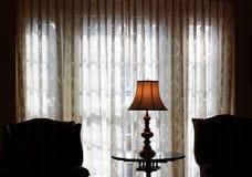 Skrivbordlampa vid fönstret Arkivbilder