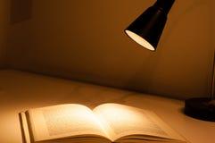 Skrivbordlampan och bokar Arkivbild