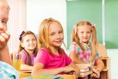Skrivbordrader med elever ser vänt rakt sammanträde Royaltyfri Fotografi