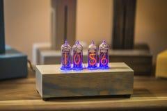 Skrivbords- klockahänder Träklocka med nummer Urladdningslampor i en genomskinlig bilaga som göras av plexiglassen Nummer som en  Royaltyfri Foto