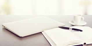 Skrivbords- kontor. Bärbar datordator, kaffe, anteckningsbok och penna