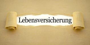 Skrivbordsarbete med det tyska ordet för livförsäkringpolitik - Lebensversicherung royaltyfri bild
