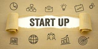 Skrivbordsarbete med start upp och affärssymboler arkivfoto
