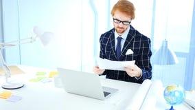 Skrivbordsarbete vid det läs- kontoret Douments för man på arbete, röda hår Royaltyfri Fotografi