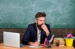Skrivbordsarbetedel av lärareliv Kontrollera läxa Läraren uppsökte hipsteren med glasögon sitter i svart tavla för klassrum arkivbild