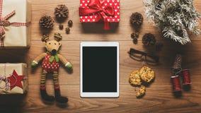 Skrivbordsikt från ovannämnt med den digitala minnestavlan och gåvor, retro xmas-begrepp för online-shopping Arkivbild