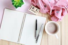 Skrivbordtabell med halsduken, öppet anteckningsbokpapper, kubkalendern och kaffekoppen Royaltyfri Fotografi