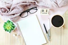 Skrivbordtabell med halsduken, anteckningsbokpapper, tillbehör, kubkalendern och kaffekoppen Royaltyfria Bilder