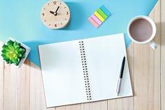 Skrivbordtabellen med den öppna anteckningsbokpapper och kaffekoppen, den bästa sikten eller lägenheten lägger med kopieringsutry Royaltyfri Bild