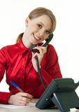 skrivbordtelefonreceptionist som ler genom att använda barn Arkivbilder