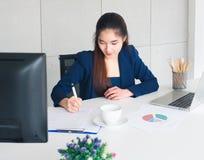 Skriver den härliga affärskvinnan för asiatiskt långt hår i den marinblåa dräkten som förbi arbetar, dokumentet på tabellen i reg arkivbilder