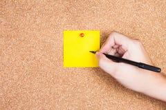 Skriver den klibbiga anmärkningen för den gula påminnelsen på korkbräde med handen till den Arkivfoton