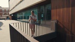 Skriver den skäggiga mannen för vuxna människan sms på skärmen av smartphonen som utomhus står stock video