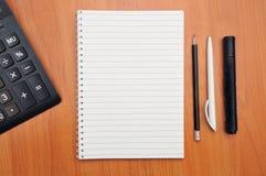 Skriver i en anteckningsbok omkring Royaltyfria Bilder