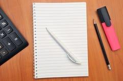 Skriver i en anteckningsbok omkring Arkivfoton