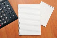 Skriver i en anteckningsbok omkring Fotografering för Bildbyråer
