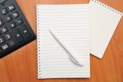 Skriver i en anteckningsbok omkring Arkivbild