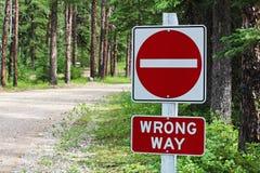 A skriver in inte, det fel vägtecknet bredvid en grusväg royaltyfri bild