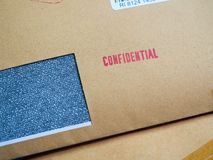 Skrivev det förtroliga `-ordet ut för röd ` på brunt tappningkuvert i makro Förtroligt begrepp för affär Royaltyfri Fotografi
