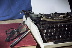 Skrivmaskin med den antika boken och glasögon Royaltyfria Bilder