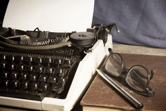 Skrivmaskin med den antika boken och glasögon, Royaltyfri Foto