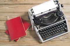 Skrivmaskin och röd anteckningsbok Royaltyfria Foton