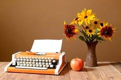 Skrivmaskinsäpplen och blommor i en vas arkivfoto
