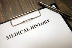 Skrivplatta med medicinsk historia och penna på skrivbordet royaltyfria bilder