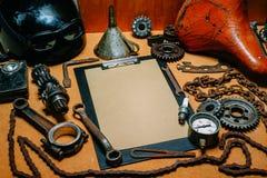Skrivplatta med pappers- For Your Information i mitten av hjälpmedel, kugghjul på tappningmetallbakgrund Motorcykelutrustning och arkivbilder