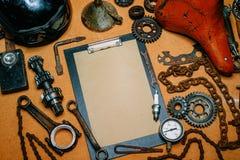 Skrivplatta med pappers- For Your Information i mitten av hjälpmedel, kugghjul på tappningmetallbakgrund Top beskådar royaltyfri bild