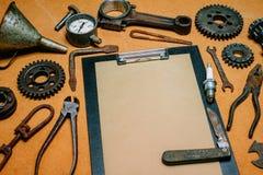 Skrivplatta med pappers- For Your Information i mitten av rostiga hjälpmedel, kugghjul på träfiberplattabakgrund Motorcykelutrust royaltyfri foto