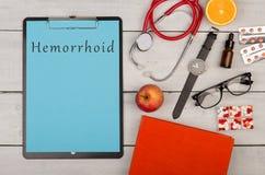 skrivplatta med text & x22; Hemorrhoid& x22; , preventivpillerar, stetoskop, bok, frukter, glasögon och klocka arkivfoton