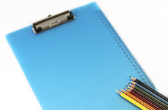 Skrivplatta och färgglade blyertspennor som isoleras på vit bakgrund Royaltyfri Bild