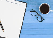 Skrivplattan med pennan, glasögon och kaffekoppen på tappning slösar wo Royaltyfria Foton