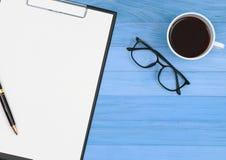 Skrivplattan med pennan, glasögon och kaffekoppen på tappning slösar wo Arkivbilder