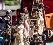 Skärm av olika afrikanska kvinnastatyetter och svarta dockor för garnering Arkivfoto