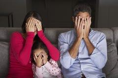 Skrämt latinamerikanskt familjsammanträde på Sofa And Watching TV Royaltyfria Bilder