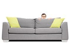 Skrämt mannederlag bak en soffa Fotografering för Bildbyråer
