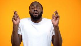 Skrockfull afrikansk amerikanmankorsning finger och be f?r bra lycka arkivfoto