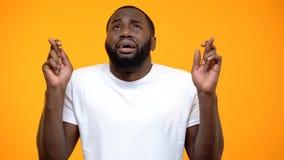 Skrockfull Afro--amerikan mankorsning finger och be till himmel, lycka fotografering för bildbyråer