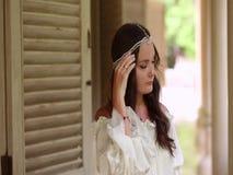Skromna młoda kobieta prostuje dekorację na jej głowie i spojrzenia w odległość zbiory wideo