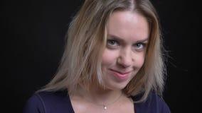Skromnie w średnim wieku blondynka bizneswoman w błękitnych bluzka zegarkach shyly w kamerę na czarnym tle zdjęcie wideo