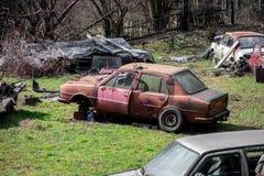 Skrotupplag på ett tidigare trädgårds- mycket av gamla övergav bilar arkivbilder