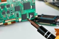 Skruv- och skruvmejselcloseup av elektronisk brädebakgrund Royaltyfri Fotografi