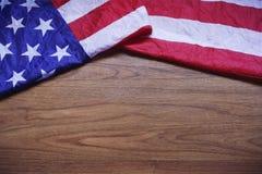 Skruvad upp USA flagga på brun träbrädebakgrund Arkivbild