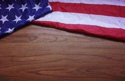 Skruvad upp USA flagga på brun träbrädebakgrund Fotografering för Bildbyråer