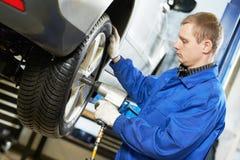 Skruvande bilhjul för auto mekaniker vid skiftnyckeln Fotografering för Bildbyråer